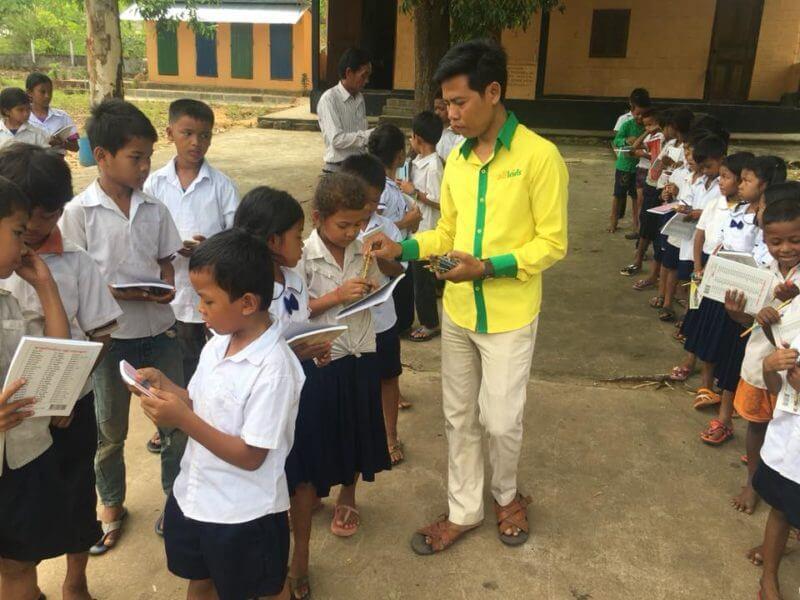 Ein Lehrer verteilt Stifte an Schüler