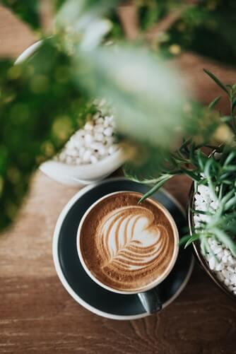 Ein Kaffee steht unter einer Blume