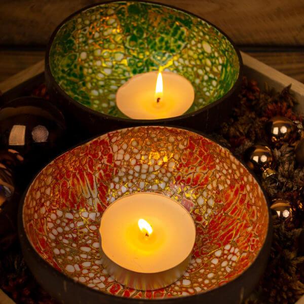 Zwei Kokosnussschalen mit jeweils grünem und rotem Muster als Behältnis für eine Kerze