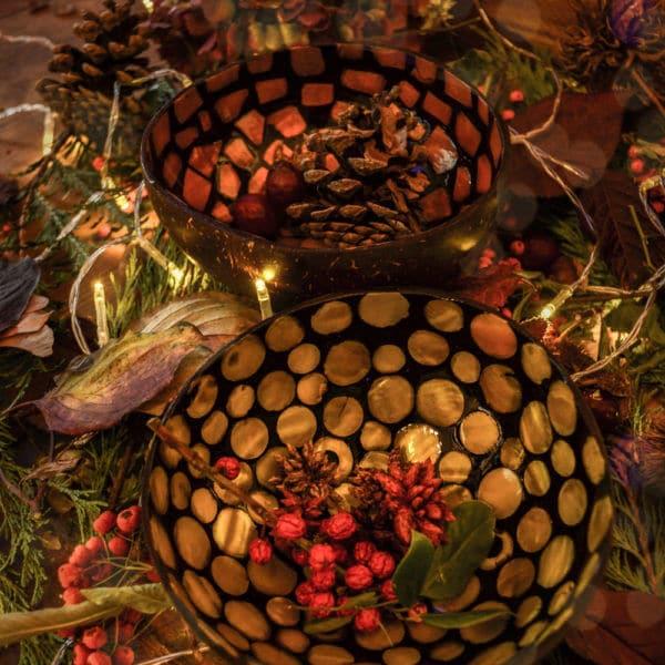 zwei Kokosnussschalen mit herbtslicher Deko umringt von Blättern und Lichterkette